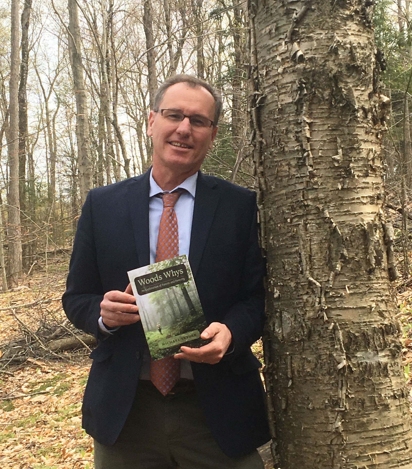 Commissioner michael snyder holding copy of Woods Whys